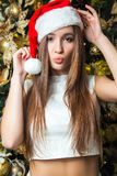 Young funny beautiful fashion model with dark eyes, brown hair and santa hat celebrating new year at home. new year decoration, wi Stock Images