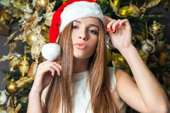 Young funny beautiful fashion model with dark eyes, brown hair and santa hat celebrating new year at home. new year decoration, wi Royalty Free Stock Photo