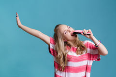 Young funny blond woman sings using pink hairbrush on blue background Royalty Free Stock Photo
