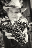 Young funny boy with bunch of grapes in hands, black and white Royalty Free Stock Photos