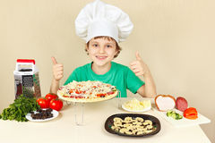 Young funny boy in chefs hat enjoys cooking tasty pizza Royalty Free Stock Photography