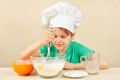 Young funny boy in chefs hat prepares the dough for baking cake Stock Photo