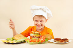 Young funny boy in chefs hat shows how to cook hamburger Royalty Free Stock Photo