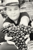 Young funny boy posing with bunch of grapes in hands, black and Stock Photo