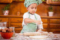 Young funny boy sprinkled flour over dough in the kitchen Stock Photo
