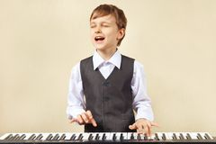 Young funny boy in suit playing the electronic organ Royalty Free Stock Photography