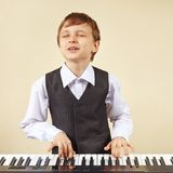 Young funny boy in a suit playing electronic synthesizer Stock Photos