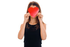Young funny brunette lady with red heart in hands posing isolated on white background. Valentines Day concept. Stock Photos