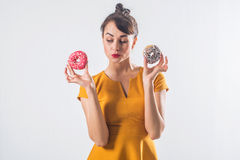 Young funny brunette model with donuts posing studio shot on white background, not isolated Stock Images