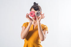 Young funny brunette model with donuts posing studio shot on white background, not isolated Royalty Free Stock Photography