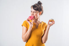 Young funny brunette model with donuts posing studio shot on white background, not isolated Royalty Free Stock Images