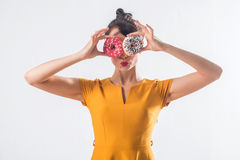 Young funny brunette model with donuts posing studio shot on white background, not isolated Royalty Free Stock Photo