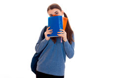 Young funny brunette student girl with backpack on her shoulders hiding her face behind a books isolated on white Stock Photo