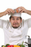 Young funny chef cracking an egg Royalty Free Stock Photography