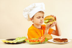 Young funny chef expressive enjoys cooked hamburger Royalty Free Stock Photography