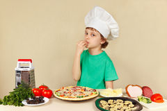 Young funny chef expressive enjoys cooked pizza Royalty Free Stock Images