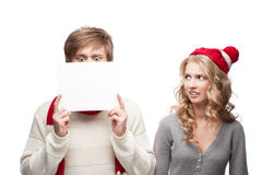Young funny christmas couple holding sign Royalty Free Stock Photography