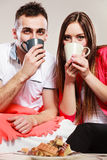 Young funny couple drinking tea or coffee Stock Images