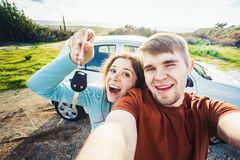 Young funny couple with keys to new car outdoor Royalty Free Stock Images