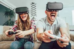 Young funny couple playing video games. Virtual reality glasses in their apartment royalty free stock image