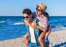 Young funny couple in sunglasses piggybacking on the beach. royalty free stock photo