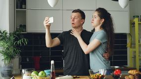 Young funny couple taking selfie photos with smartphone camera while cooking in the kitchen at home in the morning. Young funny couple taking self portrait with stock video footage