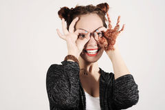 Young funny and cute hipster woman is joking and making spectacles from her hands. Royalty Free Stock Photo