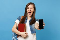 Young funny cute woman student in denim clothes with backpack blinking hold books, mobile phone with blank black empty. Screen isolated on blue background stock photos