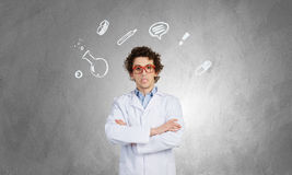Young funny doctor . Mixed media. Male doctor with curly hair wearing red glasses on concrete background Stock Photo