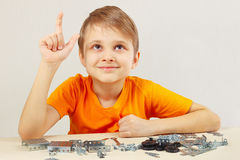 Young funny engineer thinks that assemble from mechanical constructor Stock Photo