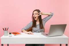 Young funny excited woman with opened mouth showing victory sign sit work at white desk with contemporary pc laptop. Isolated on pastel pink background royalty free stock photo