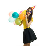 Young funny girl in bright clothes holding a lot of balloons and smiling royalty free stock photography