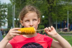 Young funny girl eating a fried corn royalty free stock photos