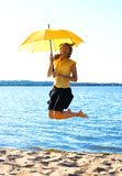 Young funny girl jumping. With an umbrella Royalty Free Stock Images