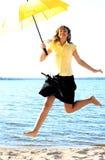 Young funny girl jumping. With an umbrella Stock Photos