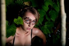 Young funny girl in party mask in forest Stock Image