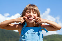 Young funny girl shows tongue Stock Image