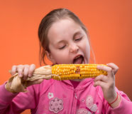 Funny girl truing to bite dry corn. Young funny girl truing to bite dry corn Stock Photos