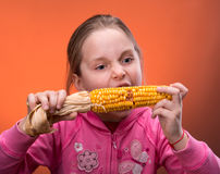 Funny girl truing to bite dry corn. Young funny girl truing to bite dry corn Royalty Free Stock Image