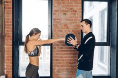Young funny girl is using a ball as a punching bag stock images