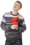 Young funny handsome man with red heart balloon. Over white Royalty Free Stock Image