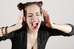 Young and funny hipster woman is screaming with hands up. Royalty Free Stock Photography