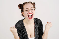 Young funny hipster woman showing tongue, shouting and surprise with funny emotion face. Studio shot with grey background Royalty Free Stock Images