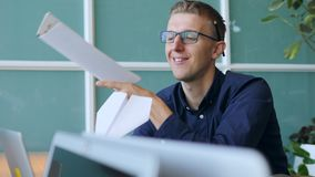 Young Funny Lazy Bad Worker Makes a Paper Airplane in Office. 4K. Young Funny Lazy Bad Worker Makes a Paper Airplane in Office. 4K stock footage