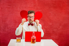 Young funny man with abstract broken heart. The young funny man with abstract broken heart on red studio background. Concept - unhappy love royalty free stock photo