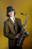 Young funny man in bowler hat holding saxophone. Portrait of young funny man in bowler hat holding saxophone. yellow background Royalty Free Stock Photo