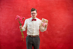 Young funny man with flowers and gift Stock Image