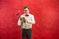 Young funny man with flowers and gift Stock Photo