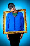 Young funny man with gold frame Royalty Free Stock Image