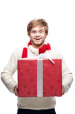 Young funny man holding christmas gift. Portrait of young funny cheerful caucasian man which holding big red christmas gift with funny expression Stock Image